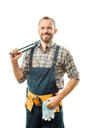 Foto de smiling plumber with tool belt holding monkey wrench and looking at camera isolated on white - Imagen libre de derechos