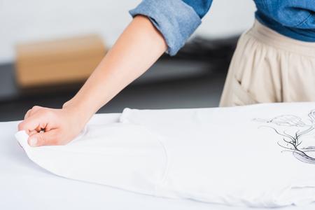 Foto de cropped image of female designer putting white t-shirt with print on ironing board - Imagen libre de derechos