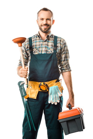 Foto de smiling handsome plumber holding plunger and toolbox isolated on white, looking at camera - Imagen libre de derechos