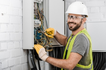 Foto de smiling handsome electrician repairing electrical box with pliers in corridor and looking at camera - Imagen libre de derechos
