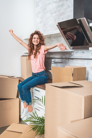 Foto de happy attractive woman with curly hair sitting on kitchen counter with outstretched hands between cardboard boxes at new home - Imagen libre de derechos