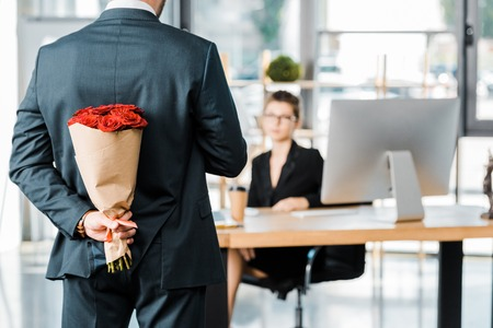 Foto de cropped image of businessman hiding bouquet of roses behind back to surprise businesswoman in office - Imagen libre de derechos