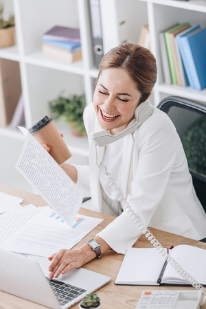 Foto de laughing businesswoman holding coffee to go while talking on phone and working with documents and laptop in office - Imagen libre de derechos