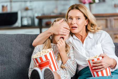 Foto de frightened mother and daughter with buckets of popcorn watching scary movie at home - Imagen libre de derechos