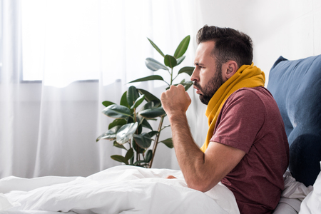 Foto de side view of sick young man having cough while sitting in bed - Imagen libre de derechos