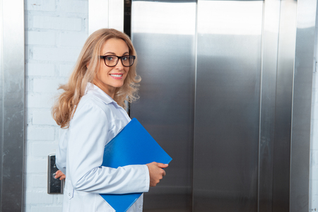 Photo pour smiling attractive lecturer pressing elevator button in medical university - image libre de droit