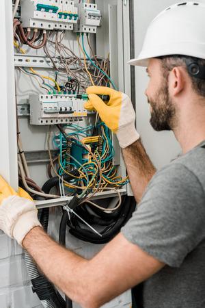 Foto de side view of electrician repairing electrical box and using screwdriver in corridor - Imagen libre de derechos
