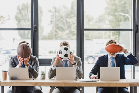 Photo pour young office workers holding balls while working with laptops in office - image libre de droit