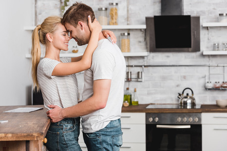 Photo pour side view of couple cuddling in kitchen and leaning on kitchen counter - image libre de droit