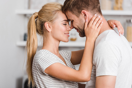 Photo pour side view of affectionate couple hugging in kitchen and touching with foreheads - image libre de droit