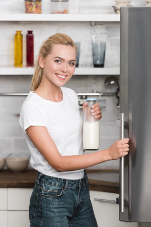 Foto de beautiful happy young woman holding bottle of milk and smiling at camera while standing near refrigerator in kitchen - Imagen libre de derechos
