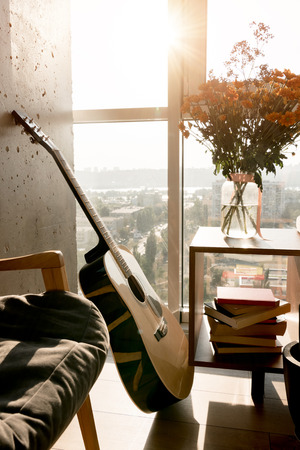Photo for close up view of acoustic guitar and beautiful bouquet of flowers at window - Royalty Free Image
