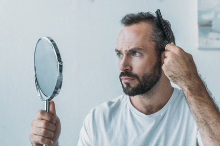 Photo pour bearded middle aged man combing hair and looking at mirror, hair loss concept - image libre de droit