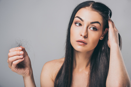 Foto de young brunette woman holding fallen hair and looking away isolated on grey, hair loss concept - Imagen libre de derechos