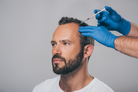 Foto de cropped shot of doctor with syringe giving injection to man with alopecia looking away isolated on grey - Imagen libre de derechos