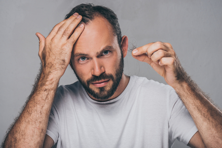 Foto de bearded middle aged man holding fallen hair and looking at camera isolated on grey - Imagen libre de derechos