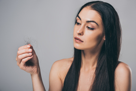 Foto de young brunette woman holding fallen hair isolated on grey, hair loss concept - Imagen libre de derechos