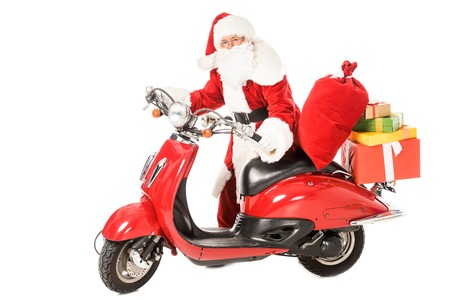 Foto de santa claus pushing vintage red scooter with sacks and gift boxes isolated on white - Imagen libre de derechos