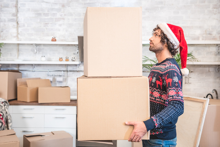 Foto de side view of young man in santa hat holding cardboard boxes during relocation - Imagen libre de derechos
