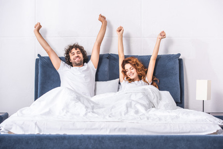 Foto de happy young couple stretching arms and waking up together in bedroom - Imagen libre de derechos