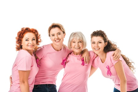 Photo pour cheerful women in pink t-shirts with breast cancer awareness ribbons smiling at camera isolated on white - image libre de droit