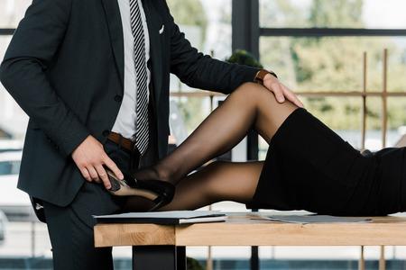 Foto de partial view of passionate businessman and businesswoman at workplace in office - Imagen libre de derechos
