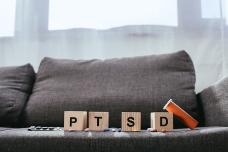 Foto de wooden cubes with posttraumatic stress disorder abbreviation signs (PTSD) lying on couch with various pills - Imagen libre de derechos