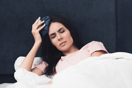 Photo for suffering sick young woman holding ice pack on head while lying in bed - Royalty Free Image