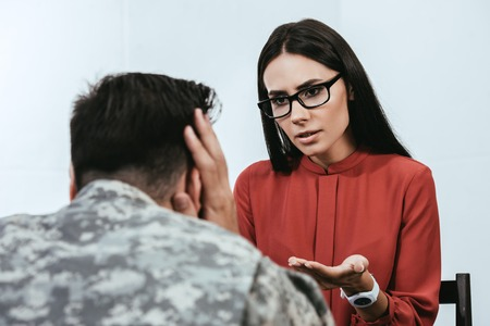 Foto de female psychiatrist talking to depressed soldier with ptsd during therapy session - Imagen libre de derechos