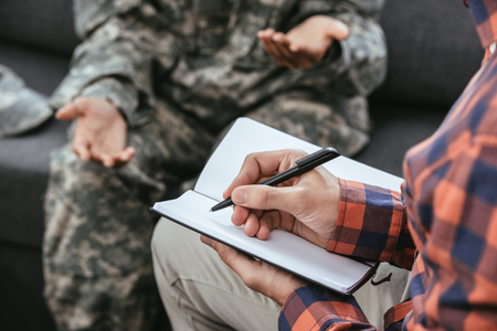 Foto de cropped shot psychiatrist writing notes during therapy session with female soldier - Imagen libre de derechos