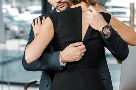 Photo pour partial view of businessman unzipping dress of seductive businesswoman in office - image libre de droit