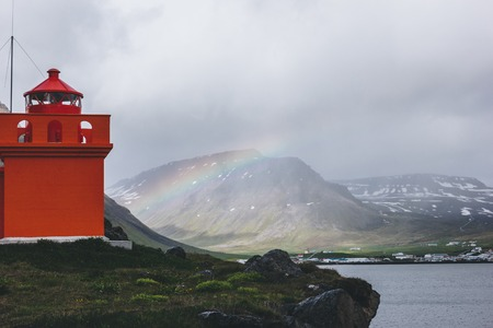 Foto de red lighthouse on cliff with rainbow on background in Iceland - Imagen libre de derechos
