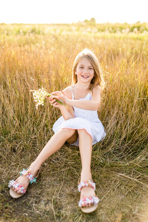 Foto de happy little child in white dress with field flowers bouquet sitting in field - Imagen libre de derechos
