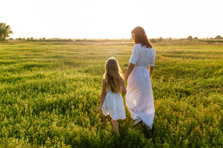 Foto de mother and daughter holding hands and walking by green meadow with sunset sky on background - Imagen libre de derechos