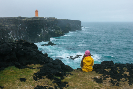 Foto de rear view of woman in yellow raincoat sitting on cliff in front of ocean and looking at lighthouse, Iceland - Imagen libre de derechos