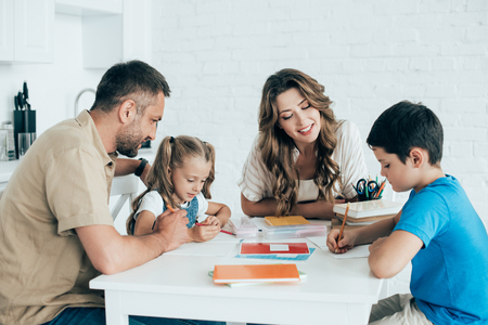 Photo for parents helping children with homework at table at home - Royalty Free Image