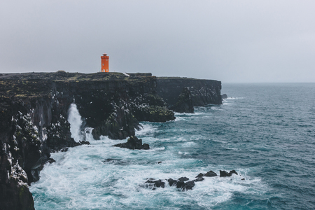 Foto de scenic shot of red lighthouse on rocky cliff in Iceland on stormy day - Imagen libre de derechos
