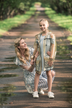 Photo for happy mother and daughter posing in transparent raincoats on wet road - Royalty Free Image