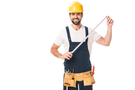Foto de handsome happy workman holding measuring tape and smiling at camera isolated on white - Imagen libre de derechos