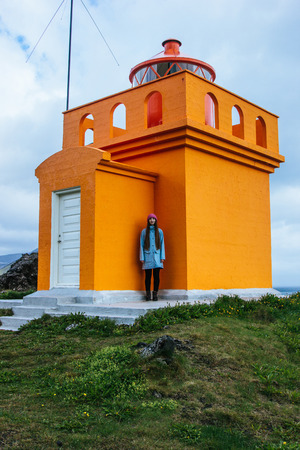 Foto de young woman standing near orange lighthouse on icelanding ocean cliff - Imagen libre de derechos