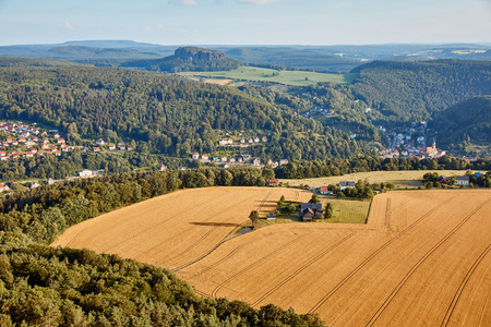 Photo pour aerial view of agricultural fields near village and mountains in Bad Schandau, Germany - image libre de droit