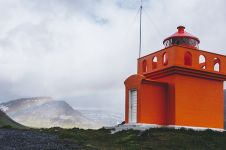 Foto de beautiful lighthouse on cliff with rainbow on background in Iceland - Imagen libre de derechos