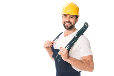 Photo pour handsome happy workman holding adjustable wrench and smiling at camera isolated on white - image libre de droit