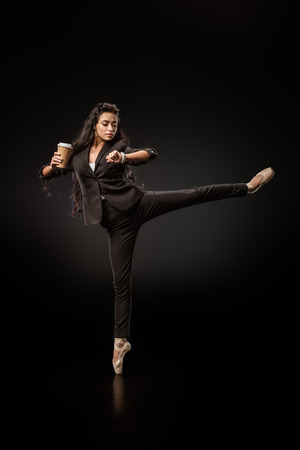 Photo for Attractive young businesswoman in formal wear and ballet shoes with coffee to go on black background - Royalty Free Image