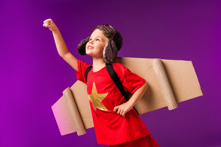 Foto de Smiling kid with plane wings and goggles standing with outstretched arm to fly isolated on purple - Imagen libre de derechos