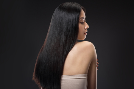 Foto de Back view of beautiful asian woman with straight and shiny hair isolated on black - Imagen libre de derechos