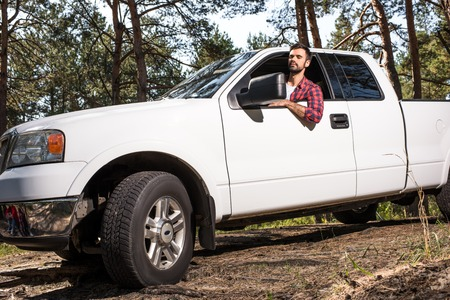 Photo pour Selective focus of young handsome man sitting in pick up car in forest - image libre de droit