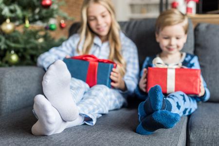 Photo pour adorable happy kids in pajamas holding gift boxes at christmas time - image libre de droit