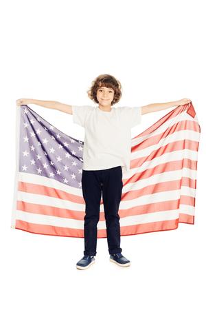 Foto de adorable preteen boy holding american flag and looking at camera isolated on white - Imagen libre de derechos