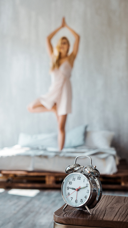 Photo for close-up view of alarm clock on wooden table and young woman performing yoga on bed behind - Royalty Free Image